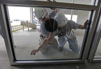 Lindsay Glass Systems workers install energy efficient panes that will help reduce the electric bill at the Lobb dealership.