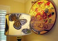 Butterflies adorn a lamp shade alongside a needlework tapestry of flowers.
