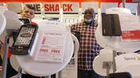Manager Ruben Zarate (left) helps customer Melvin Cheatham  select a smartphone at the RadioShack at Cityplace Market in Dallas.