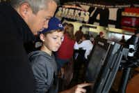 Steve Middleton  and his son, Ryan Middleton, 12, make selections on a point-of-sale computer at Mooyah in Frisco.