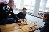 Tom Hoefer of III Forks Steakhouse and Seafood delivers a meal to Alfredo Ercoli and his wife, Kathryn Carlisle, as the couple from Rome waits for a flight at Terminal D.