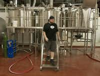 Jason Van Gilder, a brewer with Lakewood Brewing Co., descends from the stainless steel brewing tanks the company is using to brew the first batch of its Lakewood Lager.