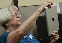 "Virginia Brackett , 75, practices using the camera app. Her instructor, Tressa Reyes, has ""the patience of a saint"" in teaching the seniors, she says."