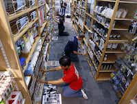 Container Store employees, Sonya Oliver, foreground, Chris Brundage, center and Lisa Kehrer,back, restock merchandise at the NorthPark store.