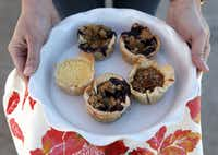 An assortment of Pie Flutin' Pastries mini pies, including blueberry crumble, black bottom pecan and lemon chess, held by owner and baker, Lindsey Crabbe at the White Rock Local Market at Lakeside Baptist Church.