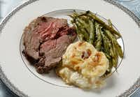 The Dallas Morning News Wine Panel on wines with the Easter meal, roast lamb and sides, photographed March 4, 2013. Roast Leg of Lamb, Potato Gratin, and Green Beans with Lemon, Garlic, and Parmigiano Gremolata. Tablecloth: Kohl's, Place Setting (flatware and china): Bed Bath and Beyond, Wine glass, alabaster eggs, and glass bowl: Williams SonomaEvans Caglage - Staff Photographer