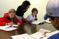 Program facilitator Janet Koslovsky helps Claire Roever, 11 (left); Victoria Alder, 12; and Joseph Ramos, 12, see the big picture.