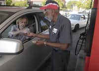Kathryn Gressett pays Lee Jennings, 68, as she stops by the Dunlap-Swain full service gas station at Cole Ave. and Monticello in Dallas Tuesday September 3, 2013. Lee Jennings has worked at the station for over forty years.