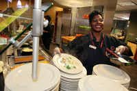 Tamerlyn Holmes, right, also known as Momma T, finishes a freshly made omelette, on Sept. 17, 2012, at the Umphrey Lee cafeteria on the campus of SMU.