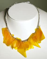 This yellow charm necklace is made from pieces of a colorful record album.