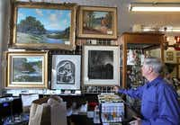 Allan Woodcock looks at some of the paintings available at Park Cities Postal Center, 3419 Westminster.