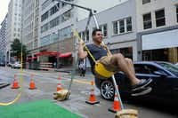 Patrick McDonnell, creative director and owner of Patrickm02L, swings on a swing-set to promote his forthcoming swing-set park in Deep Ellum at the annual Park(ing) Day promoting temporary green spaces in downtown Dallas.