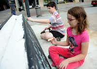 Kennedy, 9, and brother Griffin, 12,  from East Dallas, draw on the chalk boards provided by Architecture For Humanity in on Sunday during Chalk-tober Fest.Alexandra Olivia