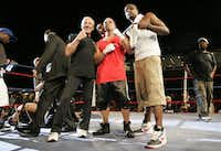 Mike Tufariello Jr. (center), of Carrollton, stands between his father, Mike Tuefariello Sr. (left), and Jamaal Lawson at center ring after the opening round of his first professional fight against Kyle Fancher.