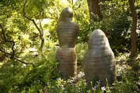 "On the property's hill are three stylized ceramic figures that seem to ""have crept in from the woods,"" Finsley says. The figures were created by Fort Worth artist Chris Powell, who has collaborated with Japanese artists."
