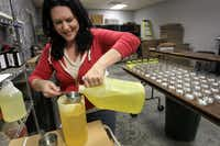 Mollie Carroll mixes the scent with the wax before pouring candles at Granny Bee's Candles in Garland.