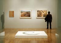 """A patron views Robert Smithson's photograph of """"The Amarillo Ramp"""" at the Dallas Museum of Art. An exhibition cointinues through April 27."""