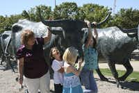 Peg Bissett (left), Katie Spangler, Justina Bissett and Kodiak Miller check out the cattle-drive sculpture in Pioneer Plaza during a Discover Dallas Tour.]