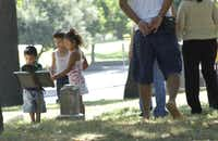 Robert, 2, (left), George, 5, (middle), and Ana Rodriguez, 4, (right) read the historical marker next to the gravesite of John and Katherine Mc Clannahan Crockett, at the Pioneer Cemetery, while site seeing with their family. The cemetery is just a few minutes walk from the Convention Center DART station, and is the resting site of many early Dallas settlers.