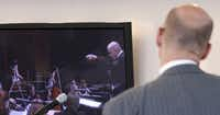 Emmanuel Villaume watches a video clip of himself conducting during Tuesday's news conference.