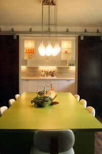 Dallas designer Katie Wietjes envisioned the custom lime-green dining table. Sliding panels on barn door tracks can close off the bar and butler's pantry.