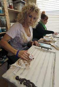 Dr. Melinda Cate of River Oaks (foreground) and Amy Shields of Fort Worth polish cabinet doors they have turned into serving trays at a class taught in Denton County by Donna Haile. Small groups participate in classes organized by the paints' local distributors.