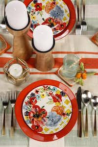 Bold Sissinghurst stoneware salad plates ($14) from Anthropologie are paired with fiery Marina dinner plates ($$9.95) from Crate & Barrel. Lagrasse table runner of jute is $28 at Anthropologie.Evans Caglage  -  Staff Photographer
