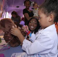 "Dr. Myiesha Taylor helps Chloe Bradley, 4, check the ears of a stuffed monkey at the Disney Jr. event, ""The Doc Mobile"" tour, highlighting the animated character, Doc McStuffins, at the Fort Worth Museum of Science and History Friday September 6, 2013. Dr. Taylor also founded the Tarrant County-based Artemis Medical Society for female doctors of color."