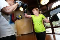 Karen Raley, 60, lands a right hand punch during her boxing class with instructor Ray Haynes, 62.