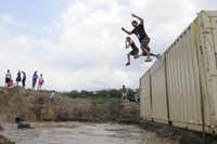 Racers leapt from a shipping container into a mud pit Saturday in the Original Mud Run  in Fort Worth.