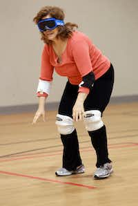 DMN writer Nancy Churnin feels her way down to the hash mark line before playing goalball.  Churnin used goggles to block out all sight while playing the game. Blind and visually impaired athletes play goalball at the Bradfield Recreation Center in Garland recently.