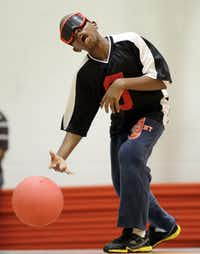 Terrence Reid-Sumter, 13, sends the 3.5 pound goalball down court.  Blind and visually impaired athletes play goalball at the Bradfield Recreation Center in Garland recently.