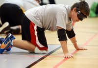 Steven Daugherty, 14, feels the tape and string placed under the tape to orient himself on the court before playing a round of goalball.  Blind and visually impaired athletes play goalball at the Bradfield Recreation Center in Garland recently.