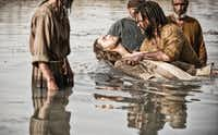 "Diogo Morcaldo (center) as Jesus is baptized by Daniel Percival, as John, in a scene from ""The Bible."""
