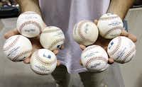 Zack Hample holds eight of the 11 balls he collected during Friday's Rangers-Red Sox game.