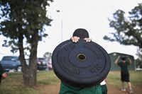 A wrestler carries his weight back to the weight room after the first portion of practice at Birdville High School in North Richland Hills, TX. on Friday Oct. 12, 2012.