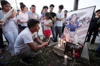 Armando Monsalve, 15, kneels in front of a portrait of longtime friend Jose Cruz, 16, during a candlelight vigil for Cruz. (Ben Torres/Special Contributor)