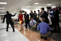 Dallas Mayor Dwaine Caraway waves goodbye to the press after making a comment following a judge's denial of his injunction request at the George L. Allen Courts Bldg. in Dallas on Tuesday.