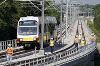 DART officials inspect a train as it rolls along during a test drive in Rowlett on Thursday.