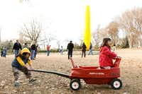 Jonas Wong, 4, and friend Sophia Wong, 5, play with with a Radio Flyer red wagon near the Yellow Icicle Tower of the Chihuly exhibit at the Dallas Arboretum. Big crowds are expected as Monday's final day nears. On Wednesday, the Chihuly team will pack up the art for shipping — a process that's expected to take about 10 days.