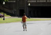 A man stood in the street near the triple underpass Wednesday to get a photo of the spot where President John F. Kennedy is believed to have been hit on Nov. 22, 1963.