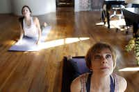 Annette Lentz teaches yoga to Lauren Batchelder (left) in the Billups Agency in Downtown Dallas.