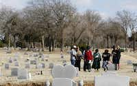 Larry Sims (center in red) along with friends and family during a small service for Sims mother at Lincoln Memorial Cemetery in Dallas.