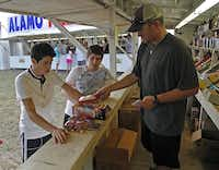 Plano residents Erick Martinez (left), 17, and Adam Jimenez, 16, are helped by Jonathan Thiebaud (right) of Stanton at the Alamo Fireworks stand on Parker Rd. in Allen on Tuesday, July 1, 2014. (Stewart F. House/Special Contributor)Stewart F. House  -  Special Contributor