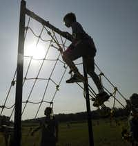 J. C. Gambill, 12, scales the 8 1/2-foot cargo climbing wall at the Wylie Junior Police Academy obstacle course.
