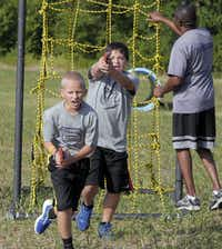 """Zach Reid, 13, (left) and Alex Ellis, 12, approach a """"dummy suspect"""" with rubber guns after climbing the cargo wall at the Wylie Junior Police Academy obstacle course. The weeklong camp was designed to give the cadets a peek at law enforcement."""