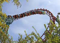 Patrons ride the Flashback at Six Flags Over Texas in Arlington. The Texas Chute Out and the Flashback rides are closing after Labor Day.