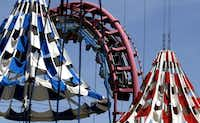 Patrons ride the Flashback at Six Flags Over Texas in Arlington. The Texas Chute Out, foreground, and the Flashback rides are closing after Labor Day.