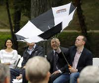 Lori Ashmore-Peters (far left) and Dallas City Council member Adam Medrano (second from right) laugh as City Council member Philip Kingston wrestles with an umbrella inverted by the wind during an Oct. 5 ribbon-cutting ceremony at Reverchon Park in Dallas. The ceremony celebrated the completion of a $2.1 million project to restore and update the park's historic stonework, built in the 1930s by Works Progress Administration crews.Michael Ainsworth - Staff Photographer