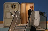 President Barack Obama smiles from onboard Air Force One as he leaves after a trip to Dallas